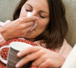 Woman with tissue and hot drink